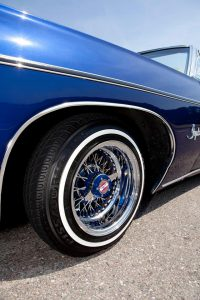 A chrome 13inch wirewheel on a blue 1968 Chevrolet Impala lowrider.